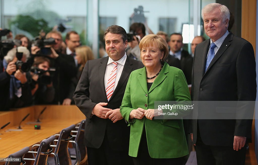 German Chancellor and Chairwoman of the German Christian Democrats (CDU) <a gi-track='captionPersonalityLinkClicked' href=/galleries/search?phrase=Angela+Merkel&family=editorial&specificpeople=202161 ng-click='$event.stopPropagation()'>Angela Merkel</a>, Chairman of the Bavarian Christian Democrats (CSU) <a gi-track='captionPersonalityLinkClicked' href=/galleries/search?phrase=Horst+Seehofer&family=editorial&specificpeople=4273631 ng-click='$event.stopPropagation()'>Horst Seehofer</a> (R) and Chairman of the German Social Democrats (SPD) <a gi-track='captionPersonalityLinkClicked' href=/galleries/search?phrase=Sigmar+Gabriel&family=editorial&specificpeople=543927 ng-click='$event.stopPropagation()'>Sigmar Gabriel</a> arrive to discuss the three parties' coalition contract with the media after signing it earlier in the day on November 27, 2013 in Berlin, Germany. The three parties worked their way through arduous negotiations on policy issues that concluded with a 17-hour overnight session last night in order to hammer out the final details that will make a new German coalition government possible. The agreement still requires approval by party delegates, which especially in the case of the SPD is uncertain.
