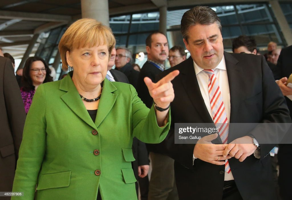 German Chancellor and Chairwoman of the German Christian Democrats (CDU) <a gi-track='captionPersonalityLinkClicked' href=/galleries/search?phrase=Angela+Merkel&family=editorial&specificpeople=202161 ng-click='$event.stopPropagation()'>Angela Merkel</a> and Chairman of the German Social Democrats (SPD) <a gi-track='captionPersonalityLinkClicked' href=/galleries/search?phrase=Sigmar+Gabriel&family=editorial&specificpeople=543927 ng-click='$event.stopPropagation()'>Sigmar Gabriel</a> depart after signing the three parties' coalition contract at the Bundestag with Chairman of the Bavarian Christian Democrats (CSU) Horst Seehofer (not pictured) on November 27, 2013 in Berlin, Germany. The three parties worked their way through arduous negotiations on policy issues that concluded with a 17-hour overnight session last night in order to hammer out the final details that will make a new German coalition government possible. The agreement still requires approval by party delegates, which especially in the case of the SPD is uncertain.