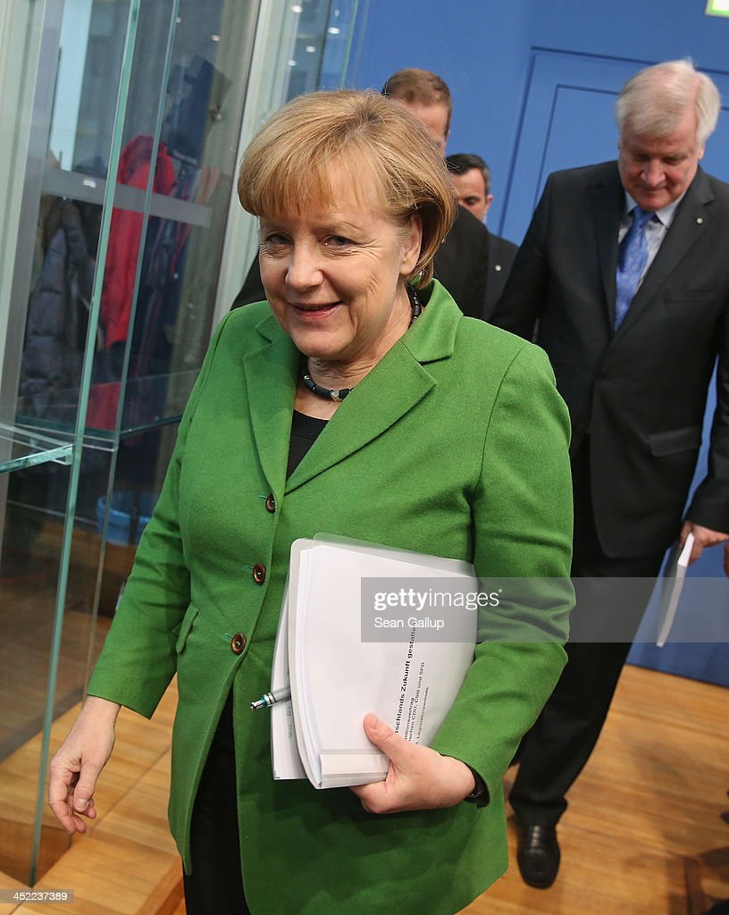 German Chancellor and Chairwoman of the German Christian Democrats (CDU) <a gi-track='captionPersonalityLinkClicked' href=/galleries/search?phrase=Angela+Merkel&family=editorial&specificpeople=202161 ng-click='$event.stopPropagation()'>Angela Merkel</a> and Chairman of the Bavarian Christian Democrats (CSU) <a gi-track='captionPersonalityLinkClicked' href=/galleries/search?phrase=Horst+Seehofer&family=editorial&specificpeople=4273631 ng-click='$event.stopPropagation()'>Horst Seehofer</a> (R) depart after they and Chairman of the German Social Democrats (SPD) Sigmar Gabriel discussed the three parties' coalition contract with the media after signing it earlier in the day on November 27, 2013 in Berlin, Germany. The three parties worked their way through arduous negotiations on policy issues that concluded with a 17-hour overnight session last night in order to hammer out the final details that will make a new German coalition government possible. The agreement still requires approval by party delegates, which especially in the case of the SPD is uncertain.