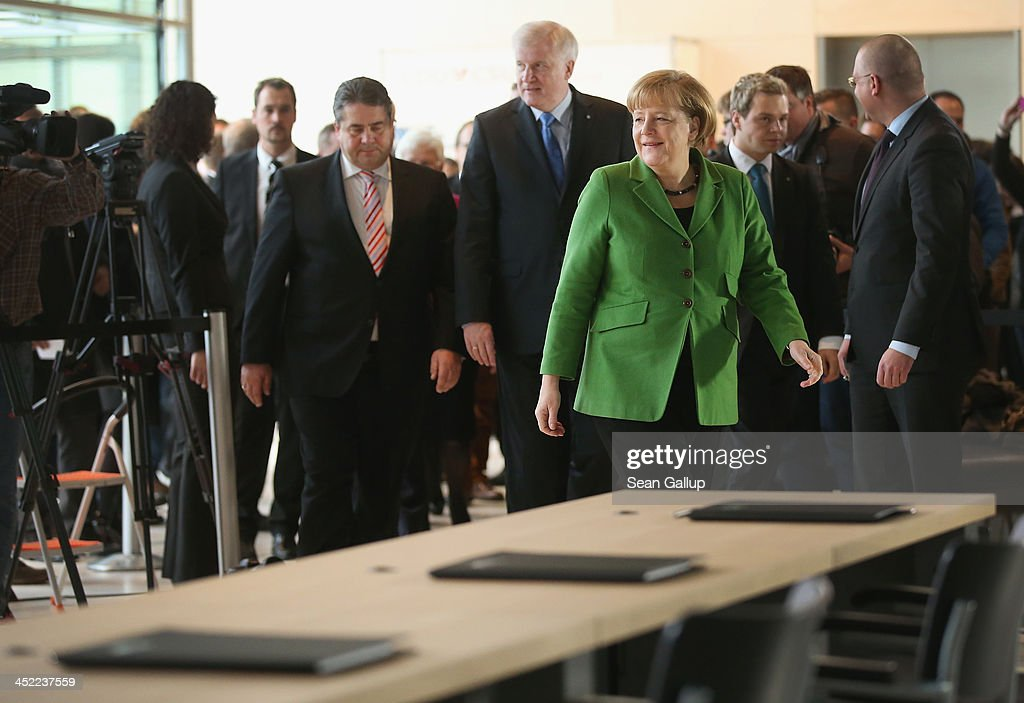 German Chancellor and Chairwoman of the German Christian Democrats (CDU) <a gi-track='captionPersonalityLinkClicked' href=/galleries/search?phrase=Angela+Merkel&family=editorial&specificpeople=202161 ng-click='$event.stopPropagation()'>Angela Merkel</a>, Chairman of the German Social Democrats (SPD) <a gi-track='captionPersonalityLinkClicked' href=/galleries/search?phrase=Sigmar+Gabriel&family=editorial&specificpeople=543927 ng-click='$event.stopPropagation()'>Sigmar Gabriel</a> (L) and Chairman of the Bavarian Christian Democrats (CSU) <a gi-track='captionPersonalityLinkClicked' href=/galleries/search?phrase=Horst+Seehofer&family=editorial&specificpeople=4273631 ng-click='$event.stopPropagation()'>Horst Seehofer</a> (C) arrive to sign the three parties' coalition contract at the Bundestag on November 27, 2013 in Berlin, Germany. The three parties worked their way through arduous negotiations on policy issues that concluded with a 17-hour overnight session last night in order to hammer out the final details that will make a new German coalition government possible. The agreement still requires approval by party delegates, which especially in the case of the SPD is uncertain.