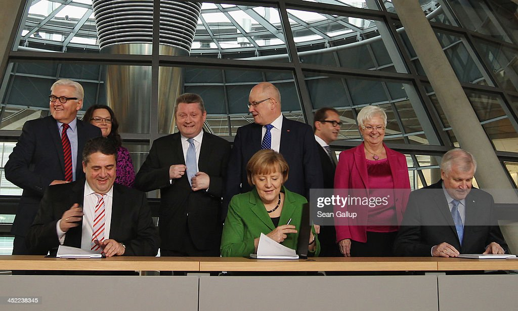 German Chancellor and Chairwoman of the German Christian Democrats (CDU) <a gi-track='captionPersonalityLinkClicked' href=/galleries/search?phrase=Angela+Merkel&family=editorial&specificpeople=202161 ng-click='$event.stopPropagation()'>Angela Merkel</a>, Chairman of the German Social Democrats (SPD) <a gi-track='captionPersonalityLinkClicked' href=/galleries/search?phrase=Sigmar+Gabriel&family=editorial&specificpeople=543927 ng-click='$event.stopPropagation()'>Sigmar Gabriel</a> (L) and Chairman of the Bavarian Christian Democrats (CSU) <a gi-track='captionPersonalityLinkClicked' href=/galleries/search?phrase=Horst+Seehofer&family=editorial&specificpeople=4273631 ng-click='$event.stopPropagation()'>Horst Seehofer</a> sign the three parties' coalition contract at the Bundestag on November 27, 2013 in Berlin, Germany. The three parties worked their way through arduous negotiations on policy issues that concluded with a 17-hour overnight session last night in order to hammer out the final details that will make a new German coalition government possible. The agreement still requires approval by party delegates, which especially in the case of the SPD is uncertain.