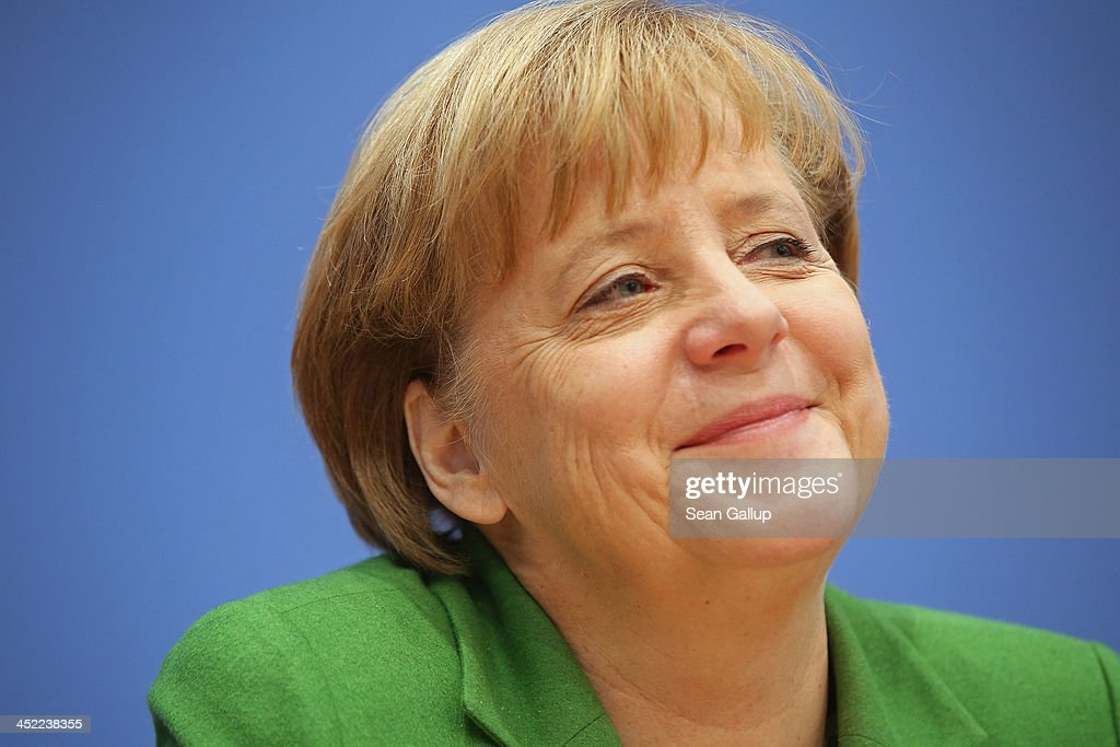 German Chancellor and Chairwoman of the German Christian Democrats (CDU) <a gi-track='captionPersonalityLinkClicked' href=/galleries/search?phrase=Angela+Merkel&family=editorial&specificpeople=202161 ng-click='$event.stopPropagation()'>Angela Merkel</a> talks to the media with Chairman of the German Social Democrats (SPD) Sigmar Gabriel and Chairman of the Bavarian Christian Democrats (CSU) Horst Seehofer (not pictured) about the three parties' coalition contract after signing it earlier in the day on November 27, 2013 in Berlin, Germany. The three parties worked their way through arduous negotiations on policy issues that concluded with a 17-hour overnight session last night in order to hammer out the final details that will make a new German coalition government possible. The agreement still requires approval by party delegates, which especially in the case of the SPD is uncertain.