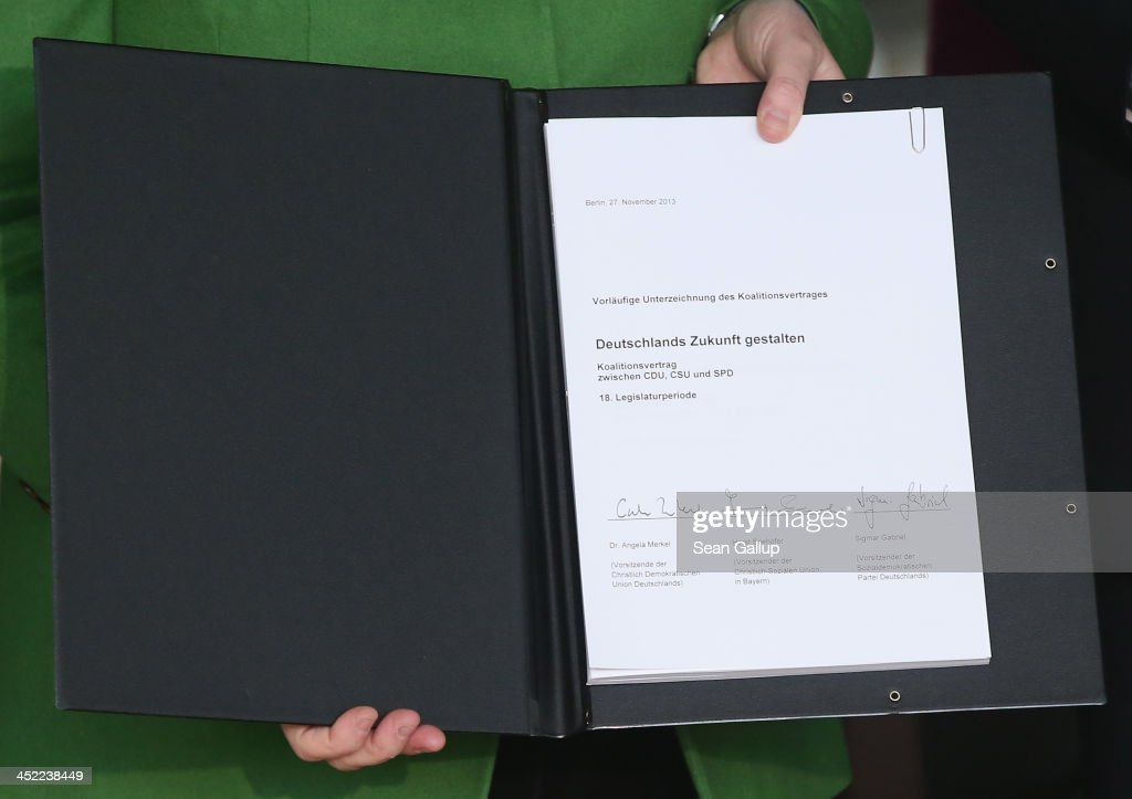 German Chancellor and Chairwoman of the German Christian Democrats (CDU) Angela Merkel hold up the three parties' coalition contract after signing it with Chairman of the German Social Democrats (SPD) Sigmar Gabriel and Chairman of the Bavarian Christian Democrats (CSU) Horst Seehofer at the Bundestag on November 27, 2013 in Berlin, Germany. The three parties worked their way through arduous negotiations on policy issues that concluded with a 17-hour overnight session last night in order to hammer out the final details that will make a new German coalition government possible. The agreement still requires approval by party delegates, which especially in the case of the SPD is uncertain.
