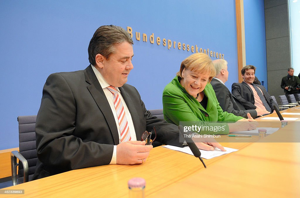 German Chancellor and Chairwoman of the German Christian Democrats (CDU) Angela Merkel (C) and Chairman of the German Social Democrats (SPD) Sigmar Gabriel (L) discuss the three parties' coalition contract with the media after signing it earlier in the day on November 27, 2013 in Berlin, Germany. The three parties worked their way through arduous negotiations on policy issues that concluded with a 17-hour overnight session last night in order to hammer out the final details that will make a new German coalition government possible. The agreement still requires approval by party delegates, which especially in the case of the SPD is uncertain.