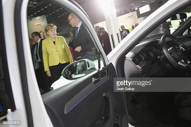 German Chancellor and Chairwoman of the German Christian Democrats Angela Merkel looks at a Volkswagen Passat GTE Variant plugin hybrid car while...