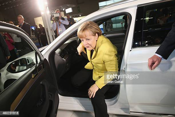 German Chancellor and Chairwoman of the German Christian Democrats Angela Merkel emerges from the driver's seat of a Volkswagen Passat GTE Variant...