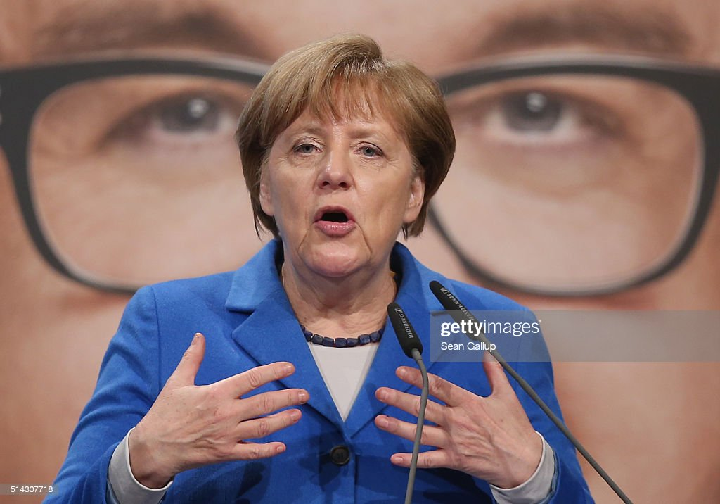 German Chancellor and Chairwoman of the German Christian Democrats Angela Merkel speaks to supporters at a CDU campaign rally in front of a billboard...