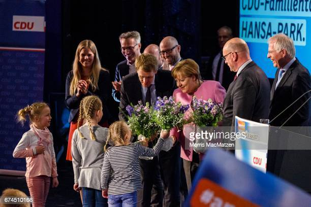 German Chancellor and Chairwoman of the German Christian Democrats Angela Merkel receives flowers as she's on stage with local CDU lead candidate...