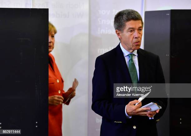German Chancellor and Christian Democrat Angela Merkel and her husband Joachim Sauer arrive to cast their ballots in German federal elections on...