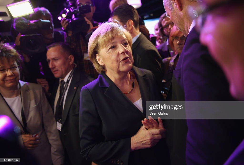 German Chancellor and Christian Democrat (CDU) Angela Merkel chats with journalists and other visitors moments after the conclusion of her live television debate with Social Democrats (SPD) chancellor candidate Peer Steinbrueck at the Adlershof studios on September 1, 2013 in Berlin, Germany. Today's live debate is the only one between the two candidates ahead of German elections scheduled for September 22.