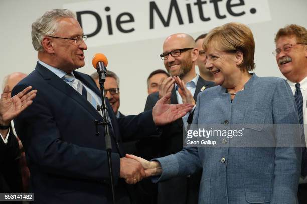 German Chancellor and Christian Democrat Angela Merkel shakes hands with leading member of the Bavarian Chrisitan Democrats Joachim Herrmann at CDU...
