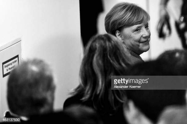 German Chancellor and Christian Democrat Angela Merkel smiles after leaving her election party and reacting to initial results that give the party...