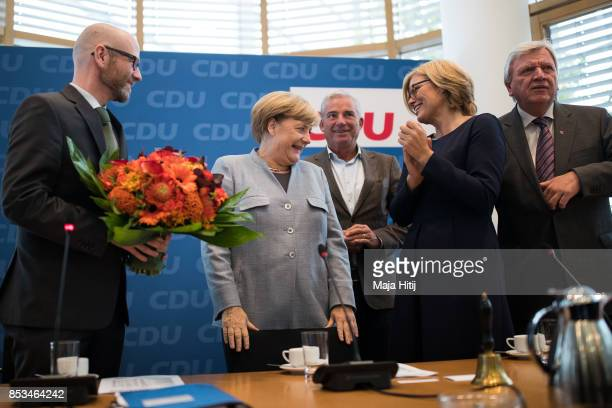 German Chancellor and Christian Democrat Angela Merkel smiles as she receives flowers from CDU Secretary General Peter Tauber at CDU headquarters day...