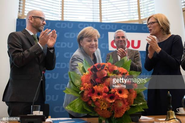 German Chancellor and Christian Democrat Angela Merkel smiles while she receives flowers from CDU Secretary General Peter Tauber at CDU headquarters...