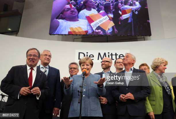 German Chancellor and Christian Democrat Angela Merkel speaks to supporters while standing next to leading members of her party and under a banner...