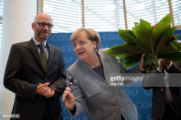 German Chancellor and Christian Democrat Angela Merkel talks while she receives flowers from CDU Secretary General Peter Tauber at CDU headquarters...