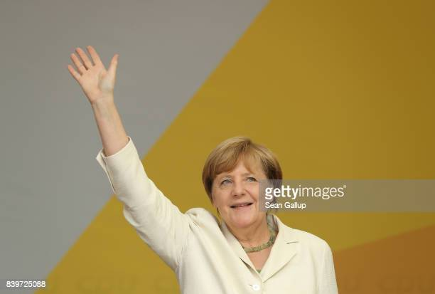 German Chancellor and Christian Democrat Angela Merkel waves to supporters after spoke at an election campaign stop on August 26 2017 in Quedlinburg...