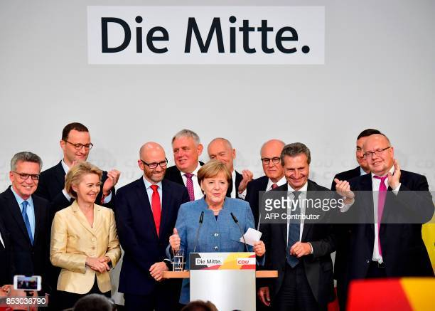 German Chancellor and Christian Democrats party leader Angela Merkel speaks on stage surrounded by her team German Interior Minister Thomas de Mazier...