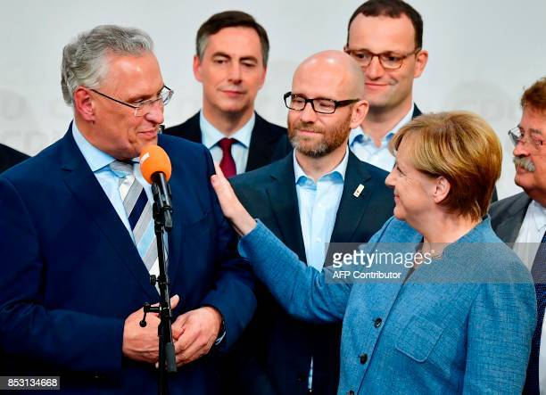 German Chancellor and Christian Democrats party leader Angela Merkel puts her hand on the shoulder of Bavaria's Interior minister and top candidate...