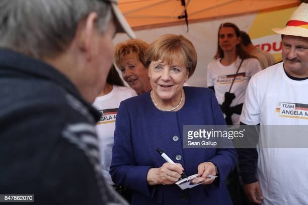 German Chancellor and Chrstian Democrat Angela Merkel signs autographs for visitors during a brief visit by Merkel to a local CDUorganized fest on...