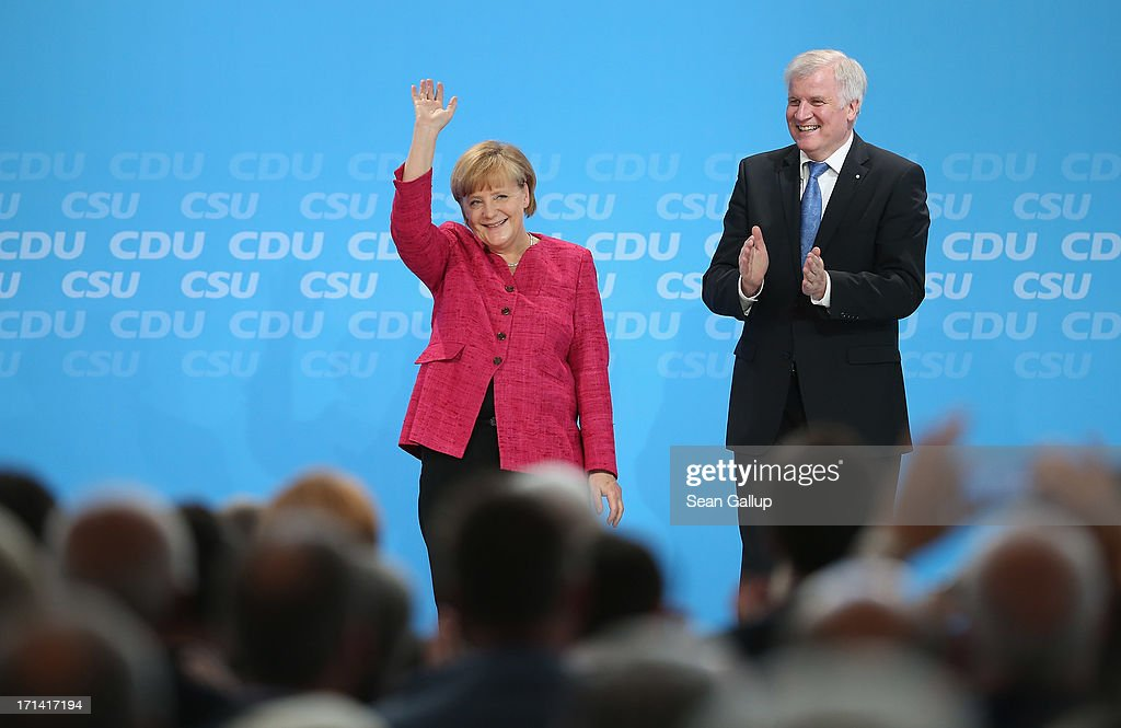 German Chancellor and German Christian Democratic Union (CDU) Chairwoman <a gi-track='captionPersonalityLinkClicked' href=/galleries/search?phrase=Angela+Merkel&family=editorial&specificpeople=202161 ng-click='$event.stopPropagation()'>Angela Merkel</a> and Bavarian Christian Social Union (CSU) Chairman <a gi-track='captionPersonalityLinkClicked' href=/galleries/search?phrase=Horst+Seehofer&family=editorial&specificpeople=4273631 ng-click='$event.stopPropagation()'>Horst Seehofer</a> receive applause after speaking at a summit of the two parties to present their election policy program on June 24, 2013 in Berlin, Germany. The two parties are in an alliance as the German Christian Democrats and currently lead in polls ahead of federal elections scheduled for September.