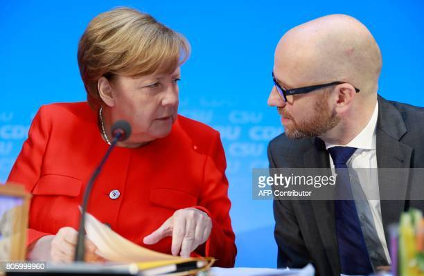 German Chancellor and head of the Christian Democrats party Angela Merkel talks with CDU Secretary General Peter Tauber prior to a meeting on July 3...