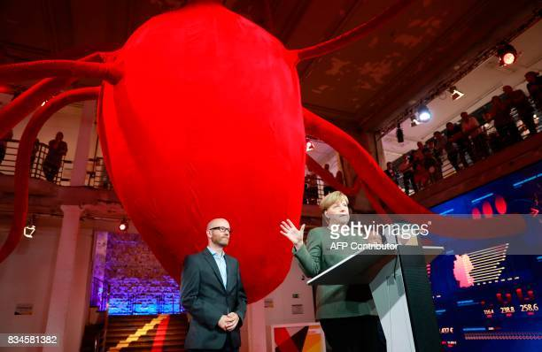German Chancellor and head of the Christian Democrats party Angela Merkel speaks in front of a giant heart mockup next to CDU Secretary General Peter...