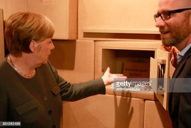 German Chancellor and head of the Christian Democrats party Angela Merkel and CDU Secretary General Peter Tauber show a mock safe as an exhibit...