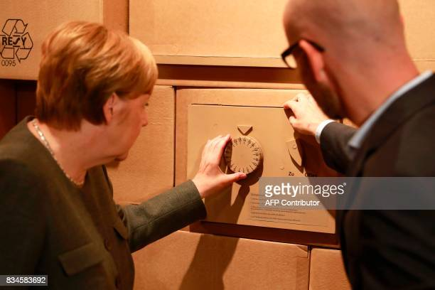 German Chancellor and head of the Christian Democrats party Angela Merkel and CDU Secretary General Peter Tauber open a mock safe as an exhibit...