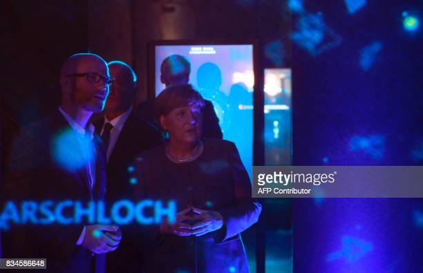 German Chancellor and head of the Christian Democrats party Angela Merkel and CDU Secretary General Peter Tauber watch an exhibit on cybermobbing...