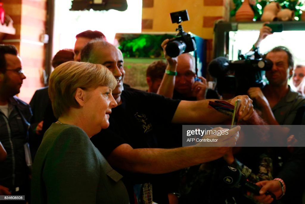 German Chancellor and head of the Christian Democrats party Angela Merkel make a selfie as she visits some shops in Berlin- Mitte district after the opening of the so-called 'walkable campaigning program' in Berlin, on August 18, 2017. / AFP PHOTO / Odd ANDERSEN