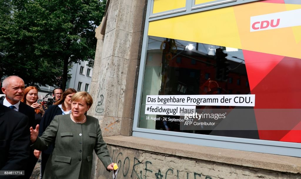 German Chancellor and head of the Christian Democrats party Angela Merkel (R) and federal whip of the CDU Klaus Schueler arrive at the house exhibiting the so-called 'walkable campaigning program' in Berlin, on August 18, 2017. / AFP PHOTO / Odd ANDERSEN