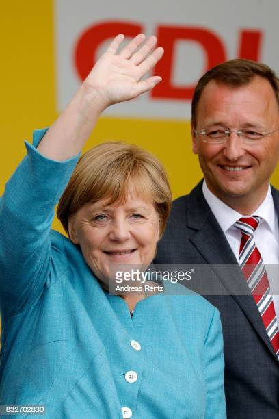 German Chancellor and head of the German Christian Democrats Angela Merkel and Josef Oster candidate for the German parliament greet supporters after...