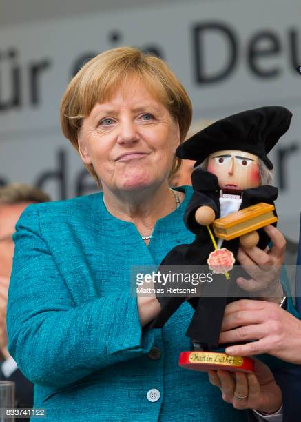 German Chancellor and head of the German Christian Democrats Angela Merkel left is handed a nut cracker in person of reformator Martin Luther after...