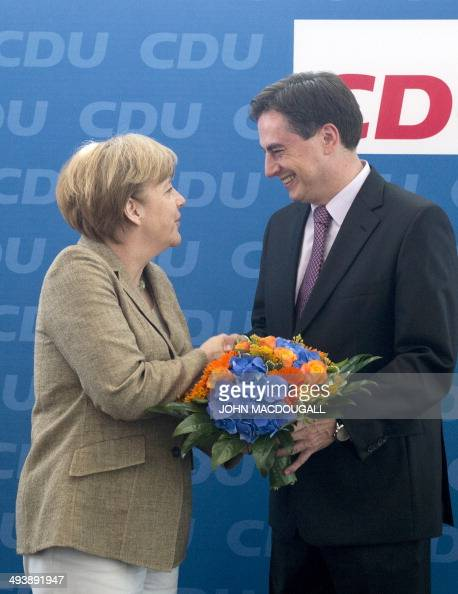 German Chancellor and leader of the Christian Democratic Union Angela Merkel congratulates the CDU's main candidate David McAllister with a bouquet...