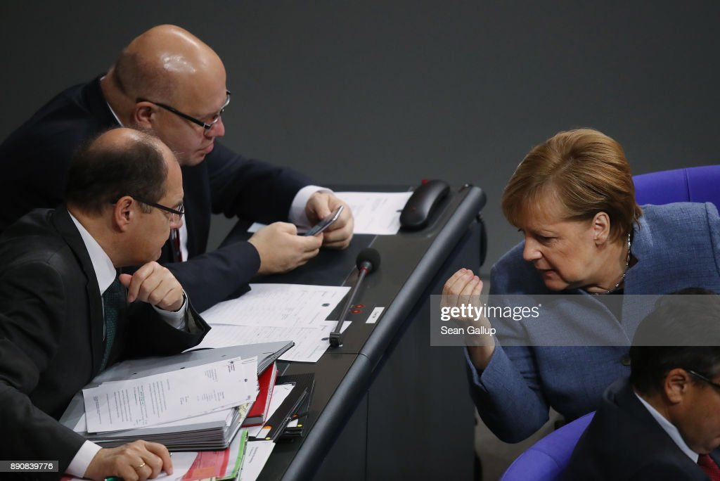 German Chancellor and leader of the German Christian Democarts (CDU) Angela Merkel (R) speaks with colleagues during debates and votes at the Bundestag over German foreign military missions on December 12, 2017 in Berlin, Germany. Merkel met in private with Martin Schulz, head of the German Social Democrats (SPD), in a room at the Bundestag during the session. Leaders of the CDU, the SPD and the Bavarian Christian Democrats (CSU) are scheduled to meet tomorrow in initial talks over the creation of a government coalition between the three parties.