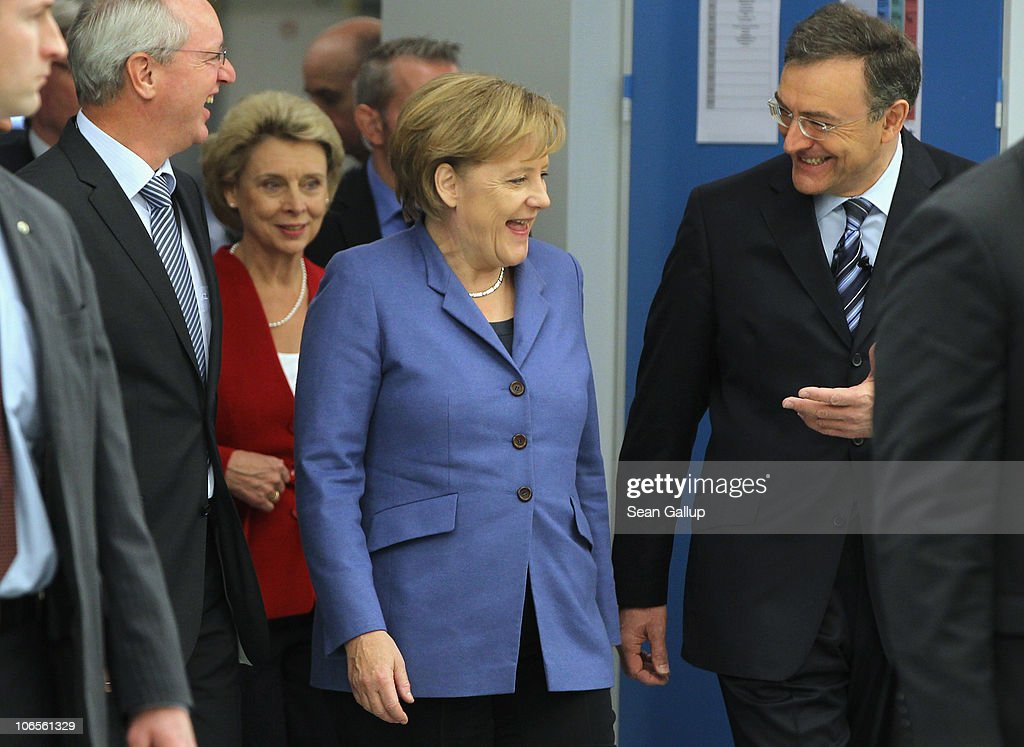 German Chancellor <a gi-track='captionPersonalityLinkClicked' href=/galleries/search?phrase=Angela+Merkel&family=editorial&specificpeople=202161 ng-click='$event.stopPropagation()'>Angela Merkel</a>, accompanied by BMW Chairman <a gi-track='captionPersonalityLinkClicked' href=/galleries/search?phrase=Norbert+Reithofer&family=editorial&specificpeople=885003 ng-click='$event.stopPropagation()'>Norbert Reithofer</a> (R), tours the BMW auto assembly plant on November 5, 2010 in Leipzig, Germany. Later Merkel and Reithofer officially inaugurated BMW's committment to invest EUR 400 million to expand production at Leipzig and to mass produce a BMW electric car.