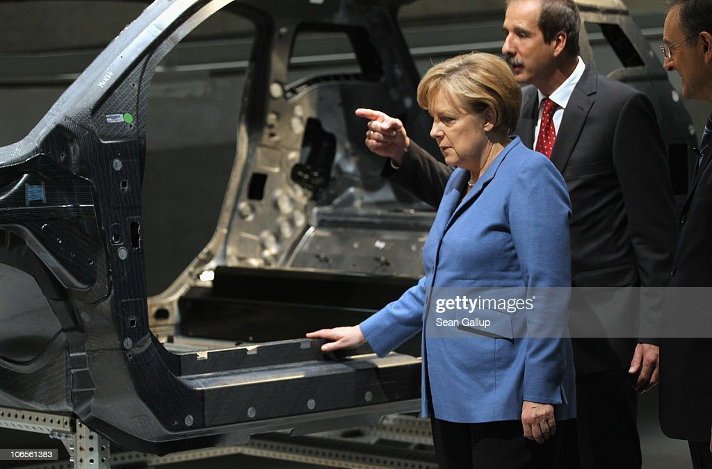 German Chancellor <a gi-track='captionPersonalityLinkClicked' href=/galleries/search?phrase=Angela+Merkel&family=editorial&specificpeople=202161 ng-click='$event.stopPropagation()'>Angela Merkel</a>, accompanied by BMW Chairman <a gi-track='captionPersonalityLinkClicked' href=/galleries/search?phrase=Norbert+Reithofer&family=editorial&specificpeople=885003 ng-click='$event.stopPropagation()'>Norbert Reithofer</a> (R) and BMW head of development Klaus Draeger, examines a carbon-fiber car body while touring the BMW auto assembly plant on November 5, 2010 in Leipzig, Germany. Later Merkel and Reithofer officially inaugurated BMW's committment to invest EUR 400 million to expand production at Leipzig and to mass produce a BMW electric car.