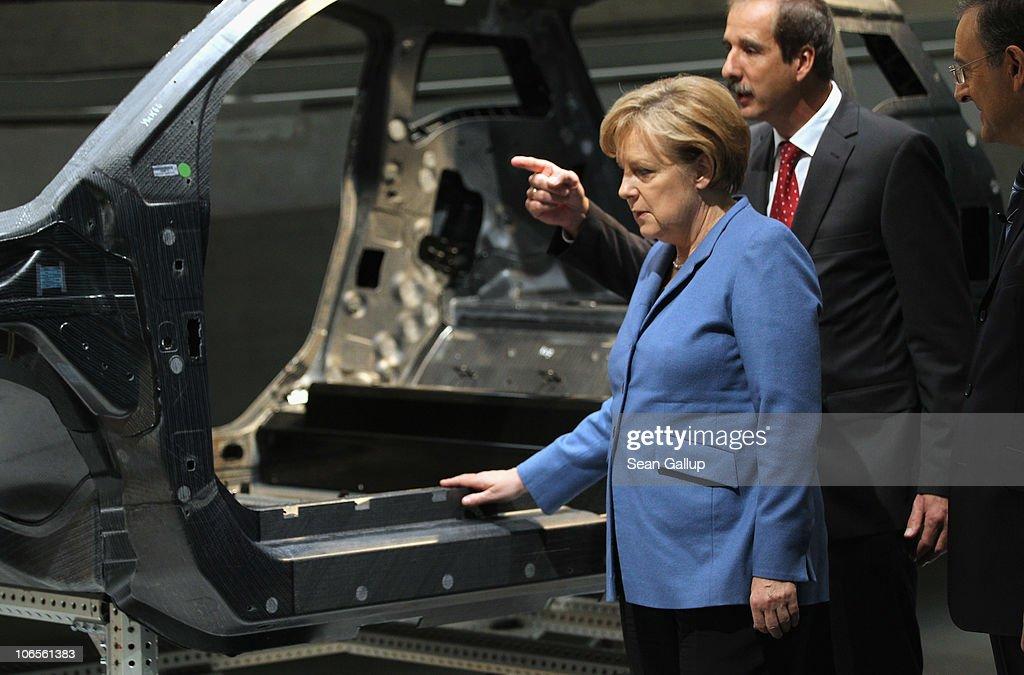 German Chancellor Angela Merkel accompanied by BMW Chairman Norbert Reithofer and BMW head of development Klaus Draeger examines a carbonfiber car...