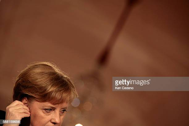 German Chancellor Angela Merkel adjusts her ear piece as she listens to President George W Bush during a joint press conference at The White House...
