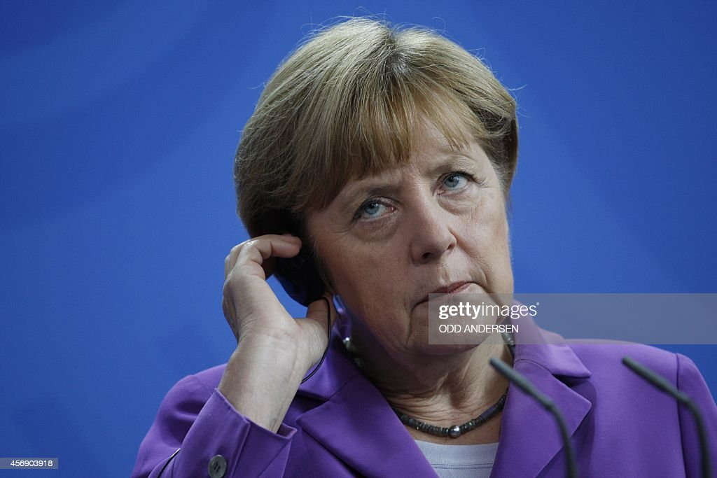 German Chancellor Angela Merkel adjusts her earpiece as she address a joint press conference with the new Polish Prime Minister after talks at the...