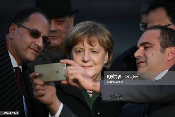 German Chancellor Angela Merkel allows Tunisian diplomats to shoot a selfie with her after she and Tunisian Prime Minister Youssef Chahed laid...