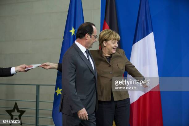German Chancellor Angela Merkel almost forgets the shake hand with French President Francois Hollande at the end of the joint press conference at...