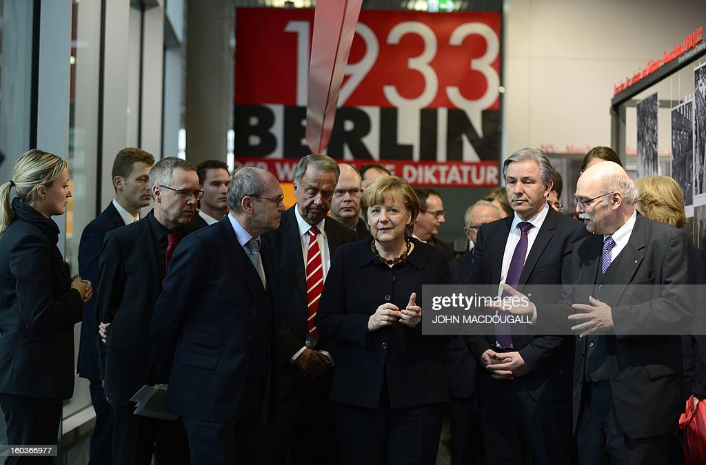 German Chancellor Angela Merkel (C) along with Berlin's mayor Klaus Wowereit (2nd R), Professor Andreas Nachama, managing director of 'Topographie des Terrors' (R), Bernd Naumann, Minister of State (4thL) and Professor Peter Steinbach, German historian and board member of the foundation, inaugurate the exhibition 'Berlin 1933 On the Path to Dictatorship', tracing Adolf Hitler's rise to power in Germany in 1933 to mark 80 years since he became chancellor on January 30, 2013 at the open-air documentation center Topographie des Terrors in Berlin. The exhibition located at the former headquarters of the Gestapo, the secret police of the Nazi regime, traces Hitler's first months in power through photos, newspapers and posters.AFP PHOTO / JOHN MACDOUGALL