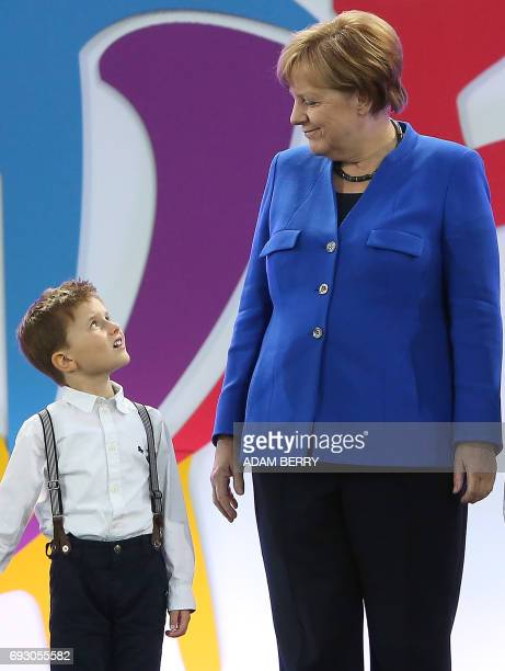 German Chancellor Angela Merkel and a young boy look at each other during the Stadium Gala of the 2017 Deutsches Turnfest at the Olympic Stadium in...
