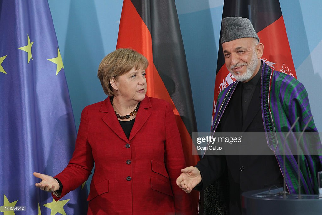 German Chancellor <a gi-track='captionPersonalityLinkClicked' href=/galleries/search?phrase=Angela+Merkel&family=editorial&specificpeople=202161 ng-click='$event.stopPropagation()'>Angela Merkel</a> and Afghan President <a gi-track='captionPersonalityLinkClicked' href=/galleries/search?phrase=Hamid+Karzai&family=editorial&specificpeople=121540 ng-click='$event.stopPropagation()'>Hamid Karzai</a> depart after speaking to the media after signing agreements on the future role of Germany in Afghanistan on May 16, 2012 in Berlin, Germany. Germany will withdraw most of its troops by 2014 but has pledged EUR 150 million in development assistance and other contributions to help Afghanistan develop its security and economy.
