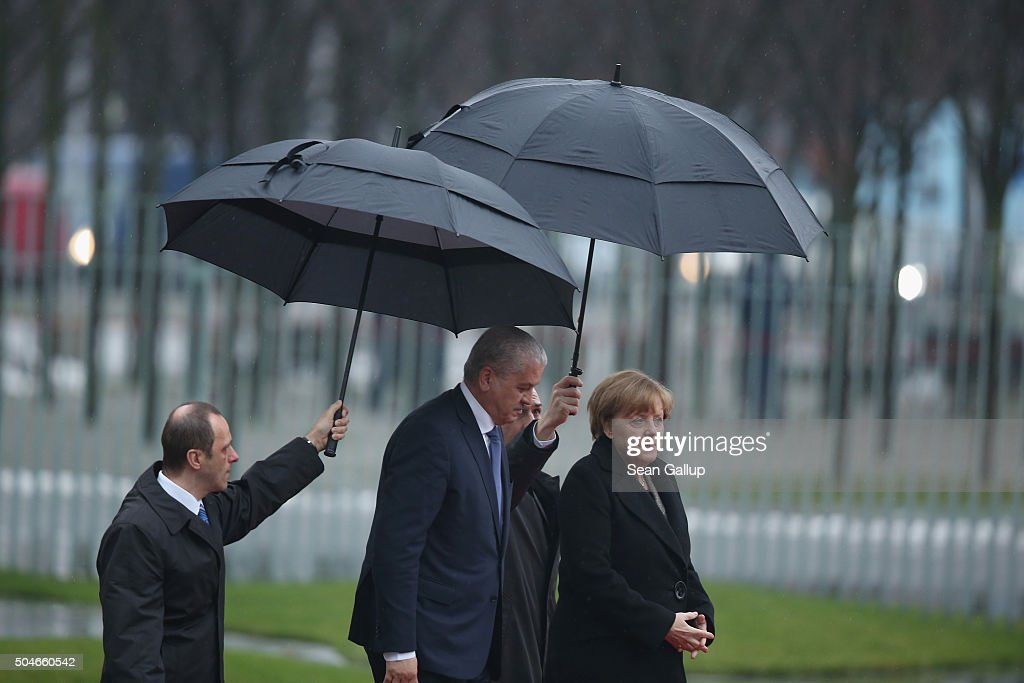 German Chancellor Angela Merkel and Algerian Prime Minister Abdelmalek Sellal walk under umbrellas as they prepare to review a guard of honour upon Sellal's arrival at the Chancellery on January 12, 2016 in Berlin, Germany. The two leaders held discussions afterwards on international and bilateral issues.