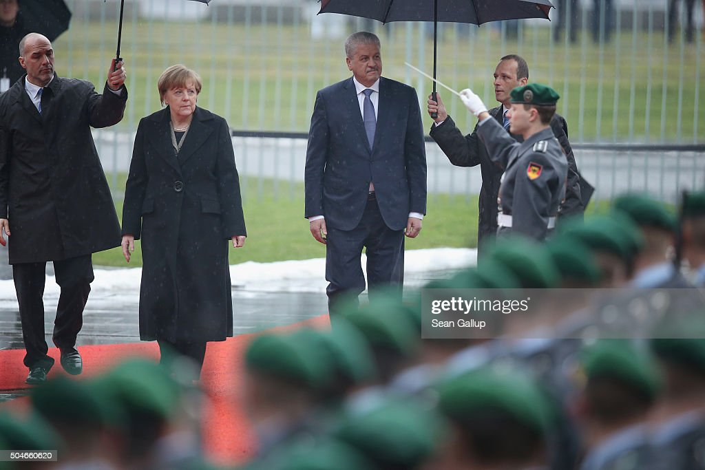 German Chancellor Angela Merkel and Algerian Prime Minister <a gi-track='captionPersonalityLinkClicked' href=/galleries/search?phrase=Abdelmalek+Sellal&family=editorial&specificpeople=3196882 ng-click='$event.stopPropagation()'>Abdelmalek Sellal</a> walk under umbrellas as they review a guard of honour upon Sellal's arrival at the Chancellery on January 12, 2016 in Berlin, Germany. The two leaders held discussions afterwards on international and bilateral issues.