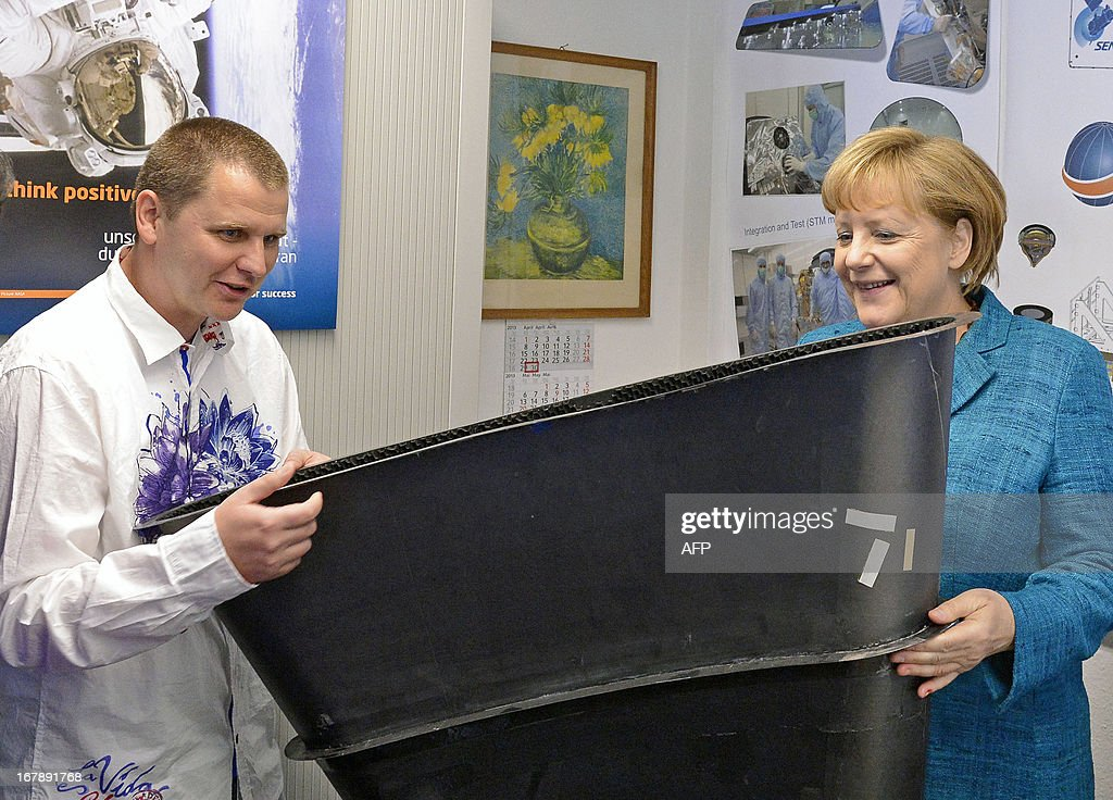 German Chancellor Angela Merkel (R) and an employee hold a carbon satellite element during her visit of Jena-Optronik GmbH (Ltd), a provider of opto-electronic instruments and sub-systems for space applications, on May 2 , 2013 in Jena, eastern Germany. AFP PHOTO / POOL/ JENS MEYER