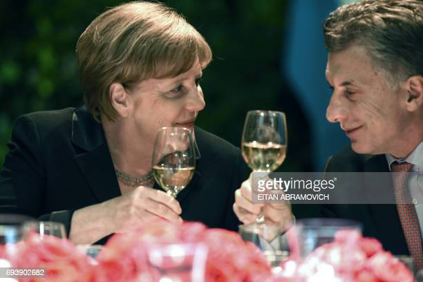 German Chancellor Angela Merkel and Argentinian President Mauricio Macri toast to each other during a state dinner at the Kirchner Cultural Centre in...